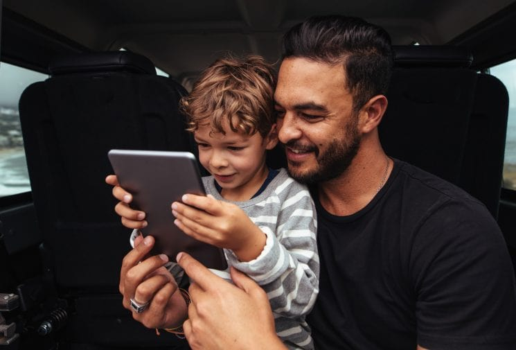 Happy father and son on road trip using digital tablet